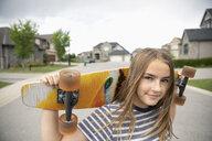 Portrait confident tween girl with skateboard on neighborhood street - HEROF12621