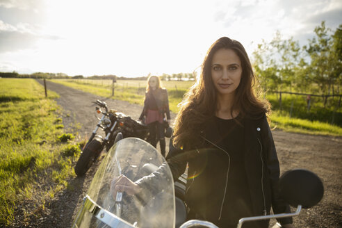 Portrait confident, cool young woman with motorcycle on sunny rural road - HEROF12633