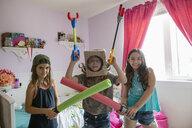 Portrait confident, playful girl friends playing, sword fighting in bedroom - HEROF12636