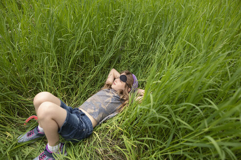 Serene girl in pirate costume laying in tall grass - HEROF12639