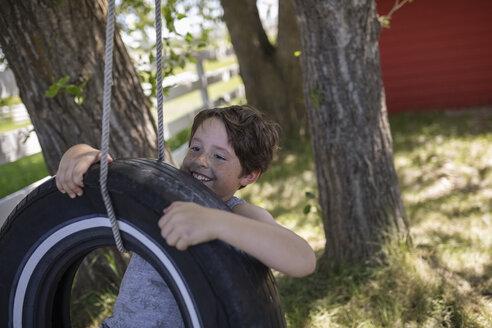 Smiling boy playing on tire swing - HEROF12651