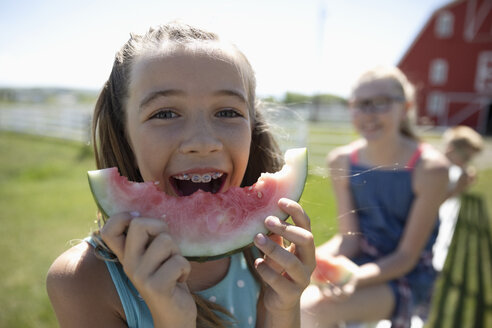 Portrait playful girl with braces eating watermelon on sunny farm - HEROF12666