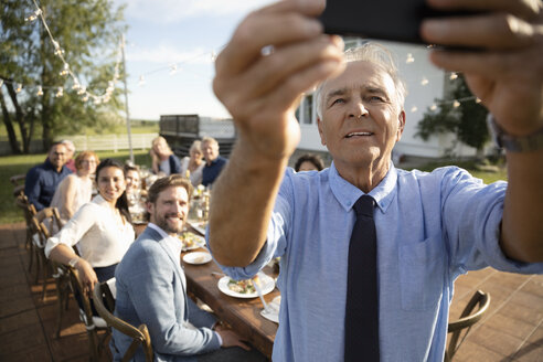 Senior man with camera phone taking selfie with friends at retirement party in sunny rural garden - HEROF12675