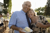 Portrait happy, affectionate couple eating cake and drinking wine, celebrating anniversary at garden party - HEROF12678