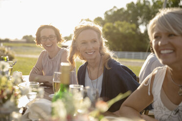 Smiling women friends drinking champagne, enjoying sunny garden party - HEROF12681