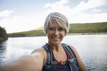 Portrait mature woman taking selfie at lakeside, Alberta, Canada - HEROF12699