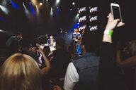 Crowd with smart phones videoing musicians performing on nightclub stage - HEROF12795