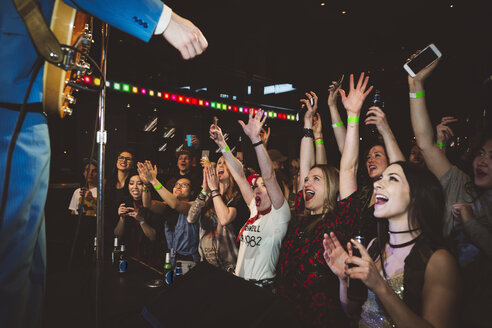 Enthusiastic millennial crowd cheering for musician at music concert in nightclub - HEROF12798