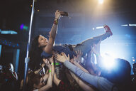 Exuberant woman with camera phone crowdsurfing at music concert in nightclub - HEROF12849
