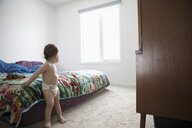 Cute baby boy in diaper in bedroom - HEROF12879