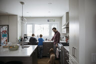 Dog watching father and sons doing dishes at kitchen sink - HEROF12882