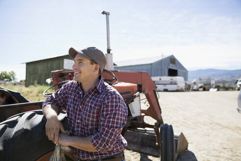 Smiling male farmer looking away at tractor on sunny farm - HEROF12957