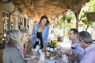 Vintner explaining wine to couples wine tasting on patio at winery tasting room - HEROF12972