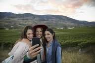 Smiling women friends with camera phone posing for selfie in vineyard - HEROF12981