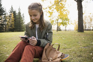 Tween girl texting with cell phone on skateboard at autumn park - HEROF13014