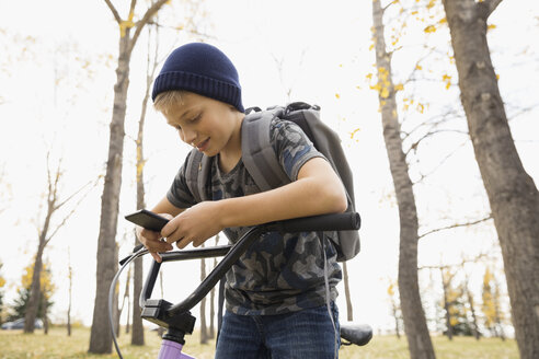 Tween boy with bicycle texting with cell phone in autumn park - HEROF13041