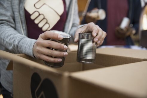 Volunteer packing tin cans into cardboard box - HEROF13062
