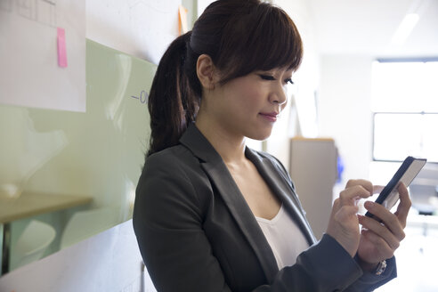 Businesswoman texting with cell phone in office - HEROF13155