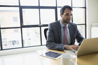 Businessman working at laptop in conference room - HEROF13164