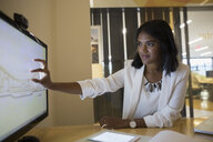 Businesswoman using touch screen monitor in conference room - HEROF13191