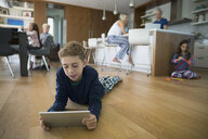 Boy in pajamas using digital tablet on hardwood floor with family in background - HEROF13209