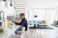 Boy eating breakfast cereal and using digital tablet in morning kitchen - HEROF13212