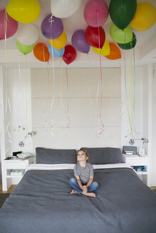 Boy on bed looking up at multicolor balloons - HEROF13227