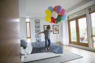 Boy with bunch of multicolor balloons jumping off bed - HEROF13230