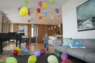 Boy running in living room with multicolor balloons - HEROF13233