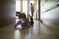 Boy laying and drawing on digital tablet on kitchen hardwood floor - HEROF13239