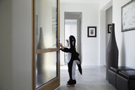Boy in killer whale costume opening front door in foyer - HEROF13245