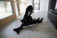 Boy in killer whale costume sitting on floor with cell phone in foyer - HEROF13248