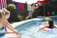 Boy jumping into sunny swimming pool - HEROF13257