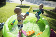Brother and sister with squirt guns in sunny wading pool - HEROF13266