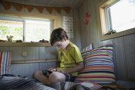 Boy using digital tablet in treehouse - HEROF13272