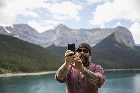 Bearded man with tattoos taking selfie with camera phone at remote mountain lakeside - HEROF13305