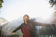 Carefree woman hiking with arms outstretched at sunny mountain lakeside - HEROF13311