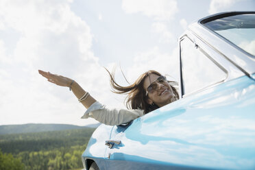 Carefree woman riding in convertible with wind blowing hair - HEROF13320