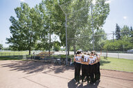 Middle school girl softball team in huddle on baseball diamond - HEROF13326