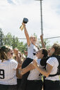 Middle school girl softball team celebrating lifting teammate holding trophy - HEROF13332