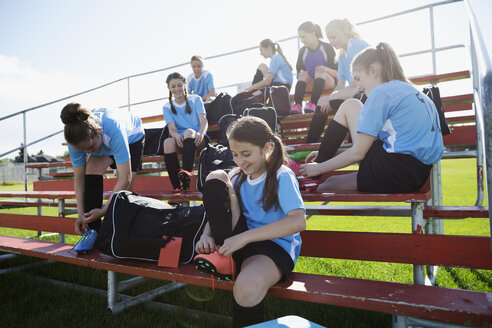 Middle school girl soccer team preparing putting on shoes on bleachers - HEROF13344