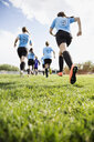 Middle school girl soccer team running onto sunny field - HEROF13353