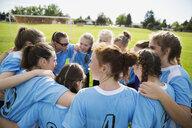 Middle school girl soccer team huddling on field - HEROF13356