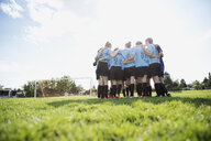 Middle school girl soccer team huddling on sunny field - HEROF13359