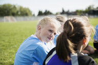 Middle school girl soccer players talking on field - HEROF13362