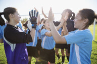 Middle school girl soccer team celebrating high fiving on field - HEROF13365
