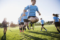 Middle school girl soccer team running drills at practice on sunny field - HEROF13371