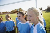 Middle school girl soccer team looking away on field - HEROF13374