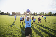 Middle school girl soccer team playing game on sunny field - HEROF13377