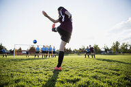 Middle school girl soccer player kicking free kick on sunny field - HEROF13380